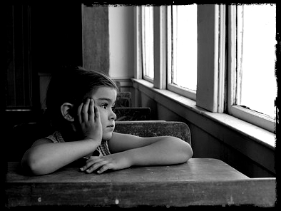 child staring school window